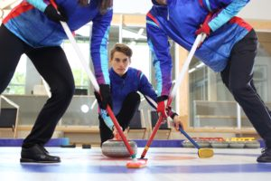 Curling, team playing on the ice